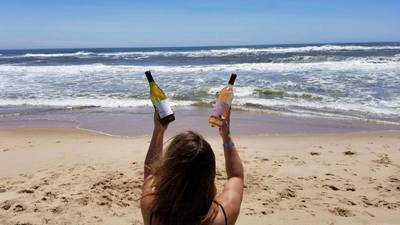 A woman holding two bottles of wine on the beach during her Hamptons weekend vacation.