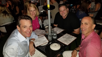 A group of professionals from NYC enjoying dinner on their Hamptons vacation.