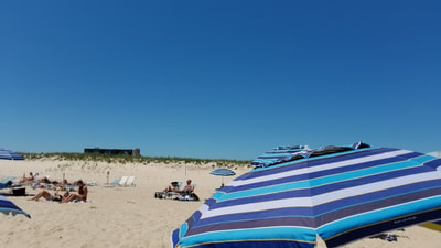 A striped umbrella on the beautiful private beach at the ocean vista hotel in the Hamptons.