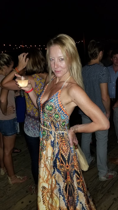 A woman with a drink in the Hamptons.