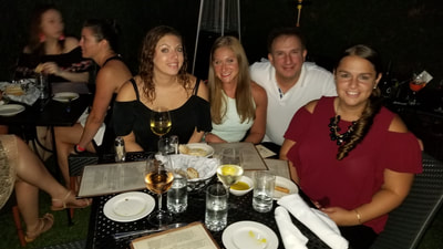 Young single NYC professionals enjoying dinner during their weekend vacation in the Hamptons.