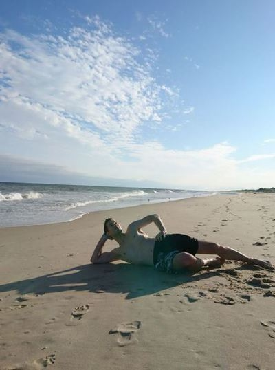 A man strikes a funny pose on a private beach in the Hamptons.
