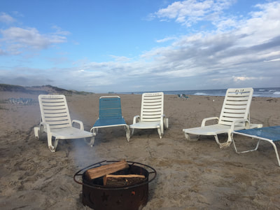 the bonfire and lounge chairs on the beach in the hamptons