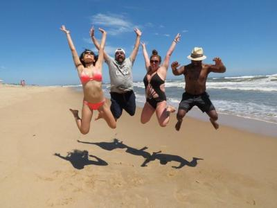 Four friends jumping on the beach during their Hamptons weekend get away.
