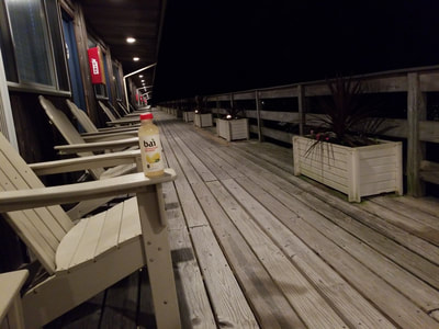 The deck of our oceanfront hotel in Montauk at night with a bai.